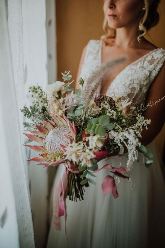 Bridal bouquet with protea, pink and burgundy flowers