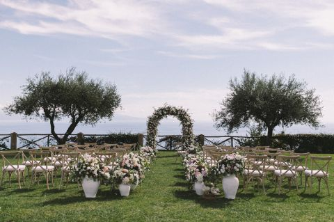 Romantic wedding ceremony with arch of flowers and decorations for the lane