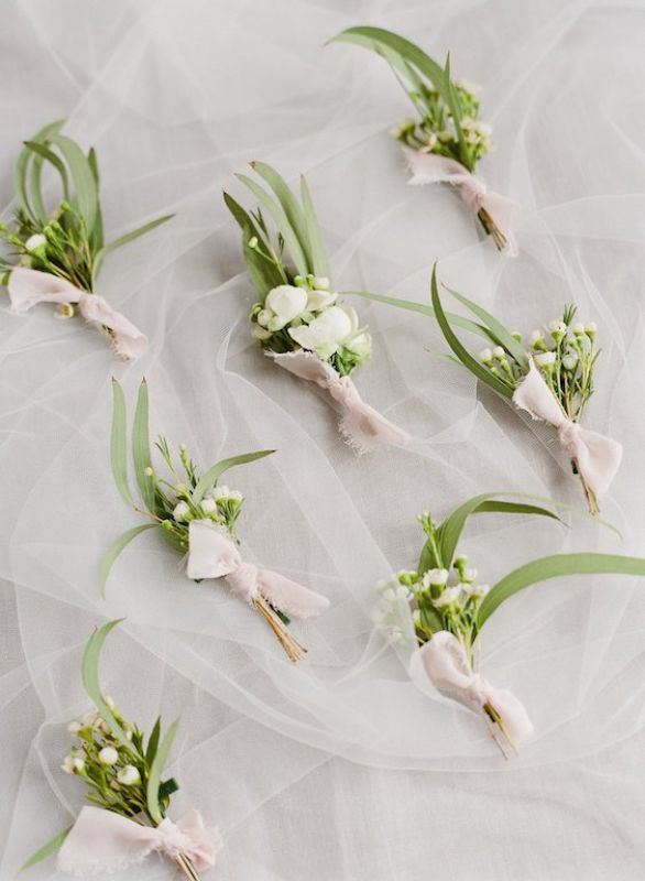 Buttonholes or buttonnieres tied with soft pink silk ribbon