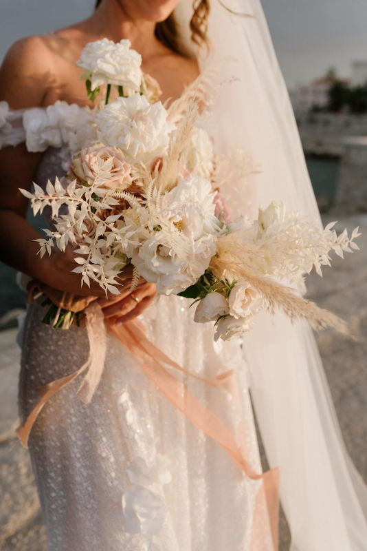 Bouquet da sposa con fiori bianchi, pampas e nastro color ruggine