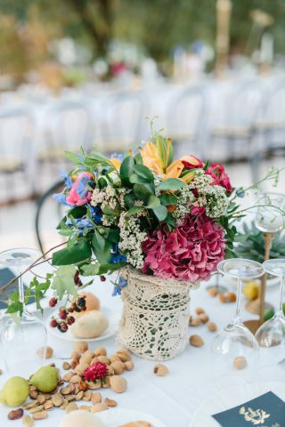 beautiful centerpiece for wedding with colorful flowers and lace pot, boho and retro style