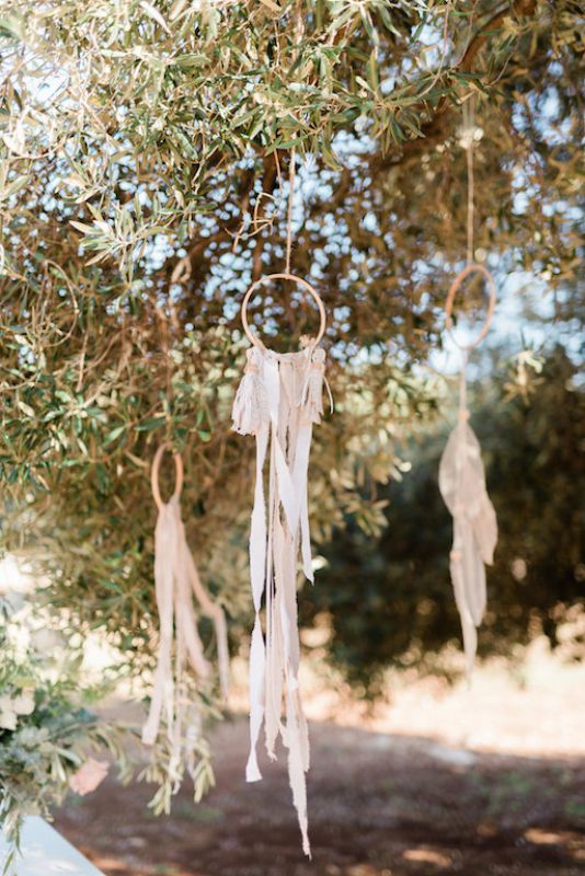 Dreamcatchers hanging from olive trees